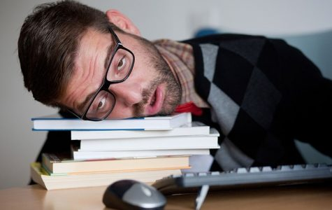 Stock image of man dozing off on stack of books