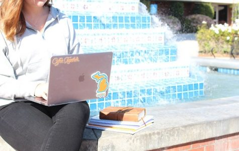 Student looking at their laptop next to Fluor fountain