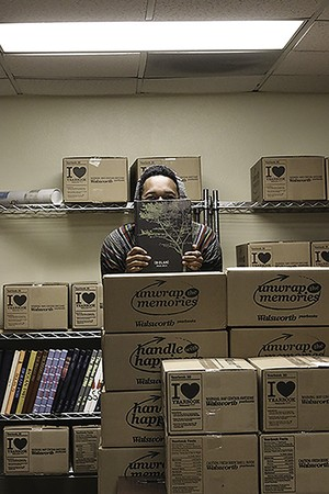 A Biolan staff member stands among boxes of fresh copies