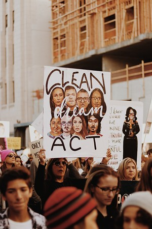 A woman holding a sign calling for a clean