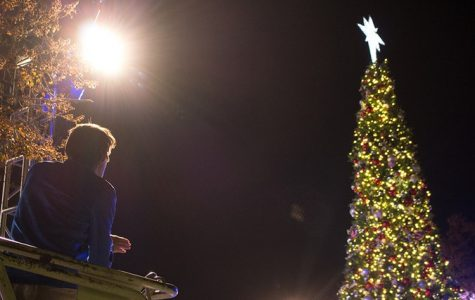 An Event Services worker looks up at the lit Christmas Tree star while preparing for the annual lighting.