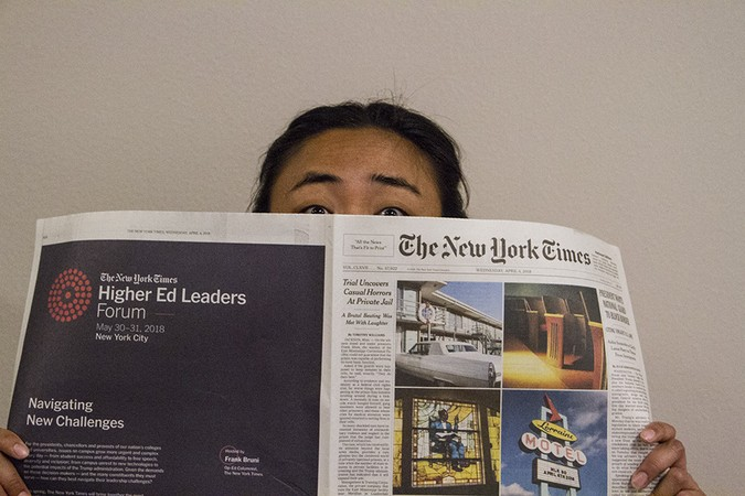 A student peeks over a copy of the New York Times
