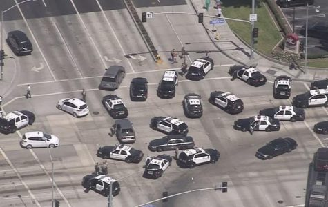 An aerial shot of several police vehicles waiting at an intersection.