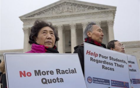 Three Asian-American protesters hold signs: