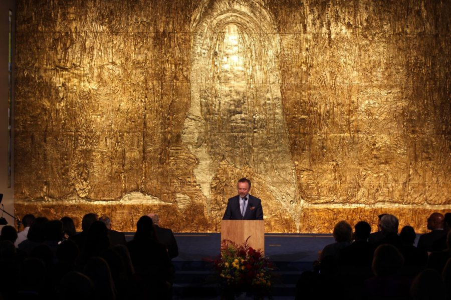 President Barry Corey stands before a 31-foot gold-adorned wall during the dedication ceremony for Calvary Chapel