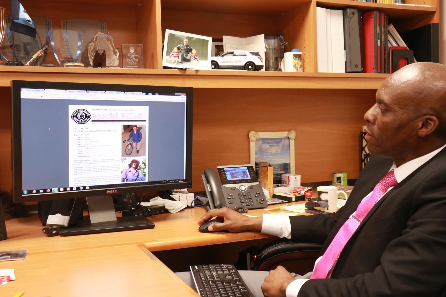 Chief John Ojeisekhoba of Campus Safety reviews an email notifying personnel of a suspect in a bike theft case.