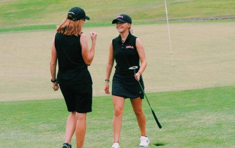 Sophia Karnazes grins on the golf green as coach Jane Carr pumps her fist into the air.