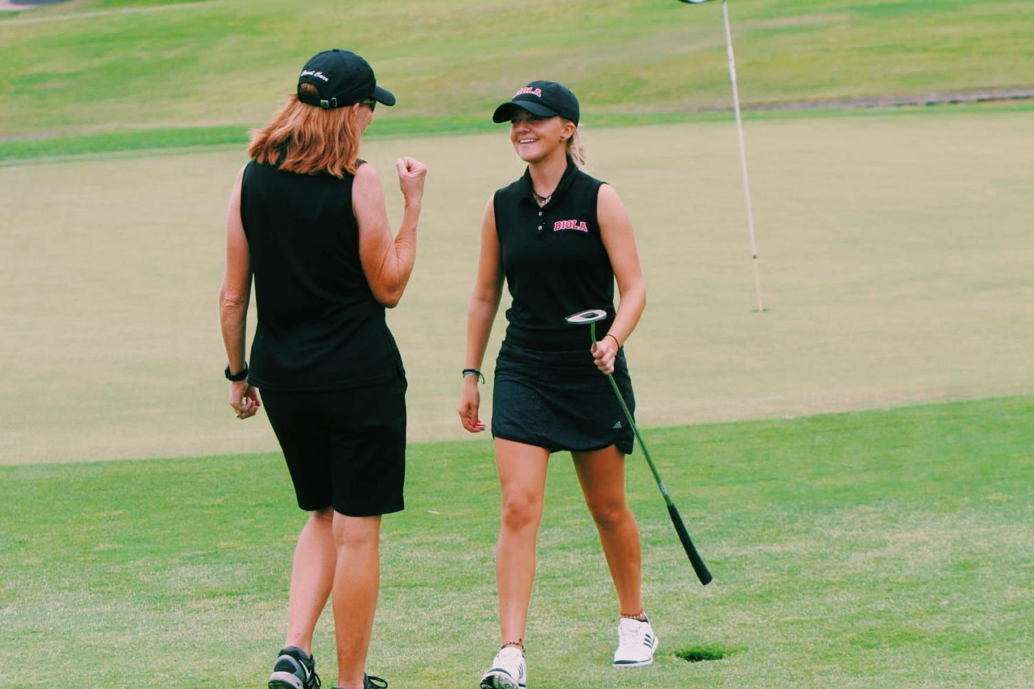 Sophomore golfer Sophia Karnazes celebrates with coach Jane Carr after shooting her first even round of her collegiate career during the NCCAA West Regional on Oct. 1.