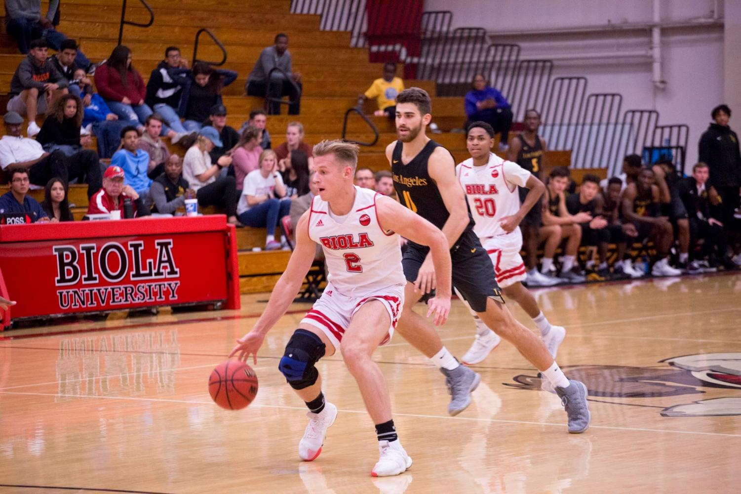 Junior forward Levi Auble dribbles past a Cal State LA defender on November 10, 2018.
