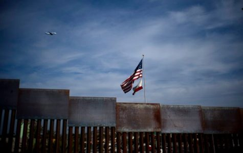american flag over border wall