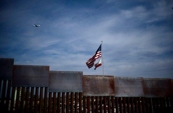 american flag over border wall