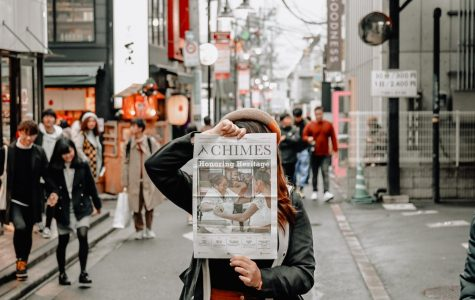 a person holding up a copy of the chimes in a busy street