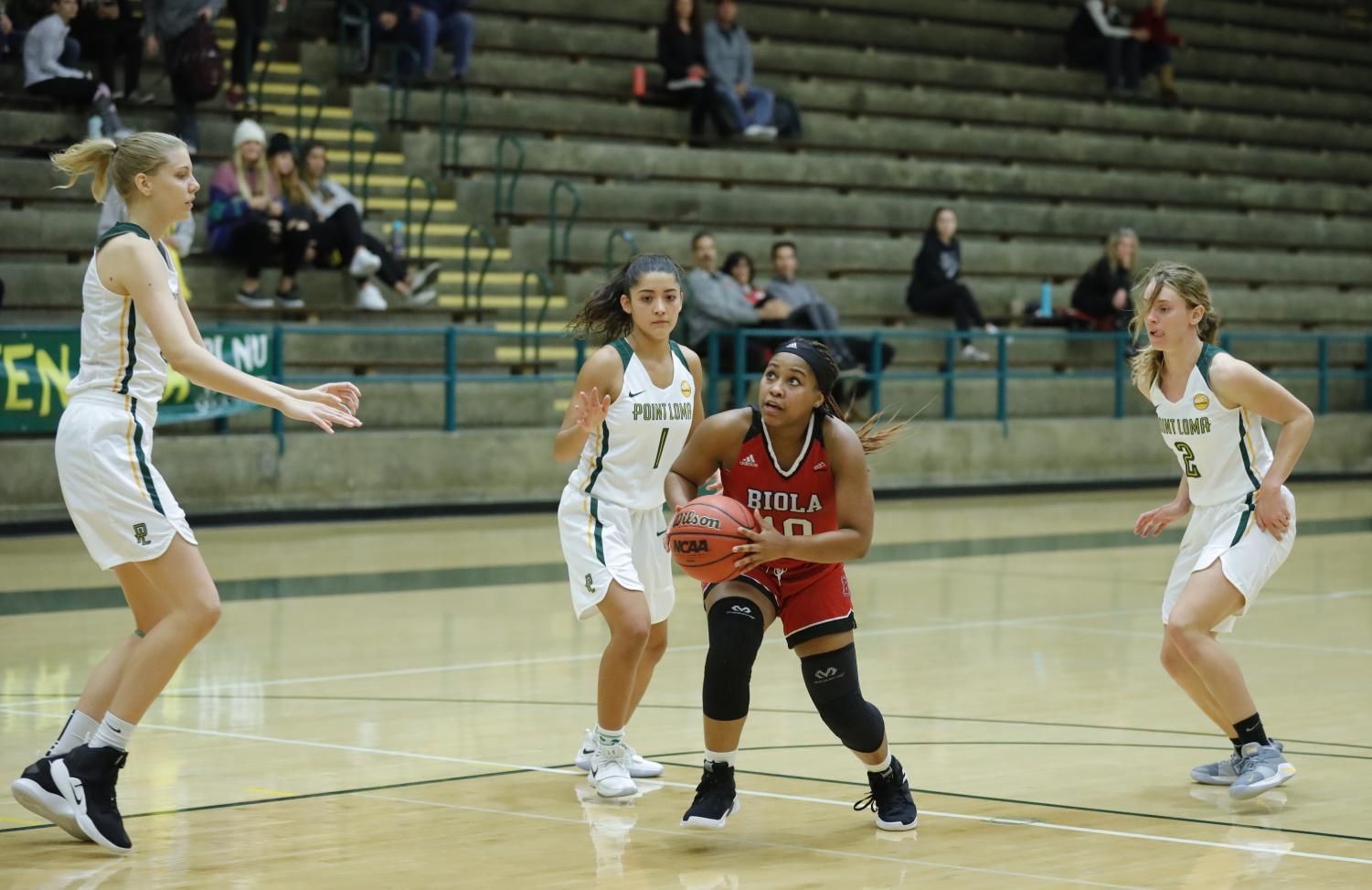 Junior guard Tatum Brimley drives past Point Loma defenders during the Eagles' 60-53 loss at PLNU on Dec. 5, 2018.