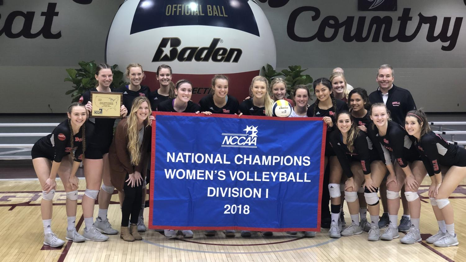 Biola volleyball players pose with the NCCAA championship banner following the Eagles' second consecutive title on Dec. 1, 2018.