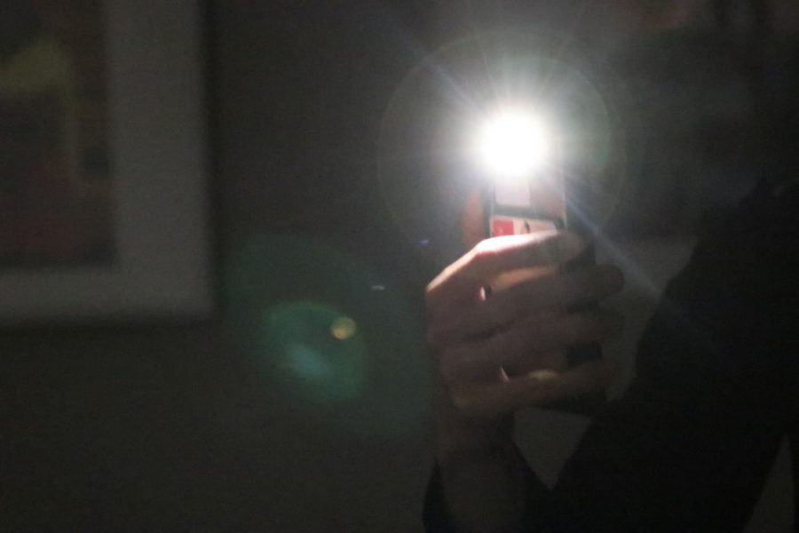 photo shows student in dark room with cell phone light on