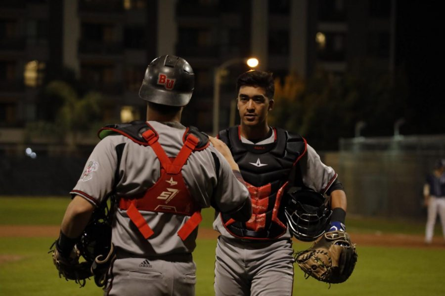 Freshman catcher Caleb Watson (left) greets freshman catcher Andrew Buglino (left) during the Eagles' 14-3 loss to Hope International University on Feb. 19.