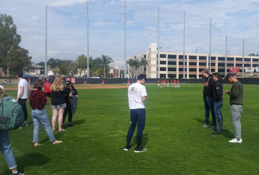 Students stand in the baseball field after being evacuated from lower campus due to a major gas leak.