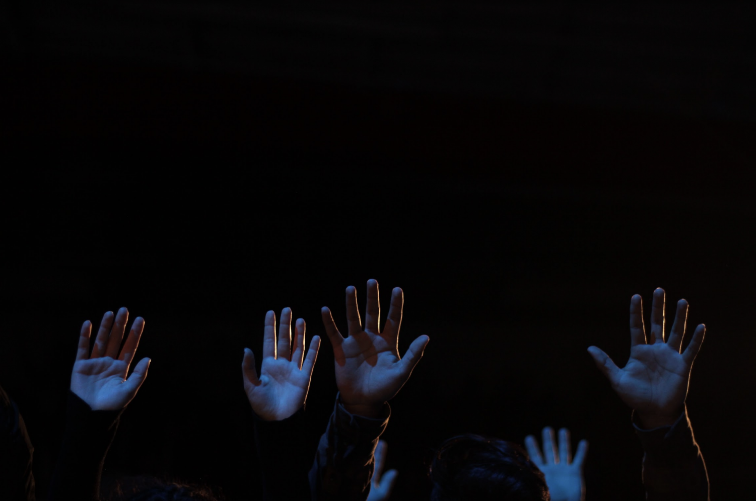 Students+raise+their+hands+in+a+position+of+surrender+during+extended+worship.