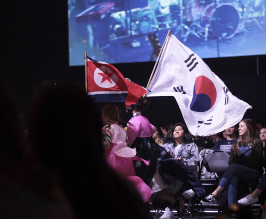 Students+in+traditional+Korean+clothing+run+the+North+and+South+Korean+flags+together+in+the+Parade+of+Nations.