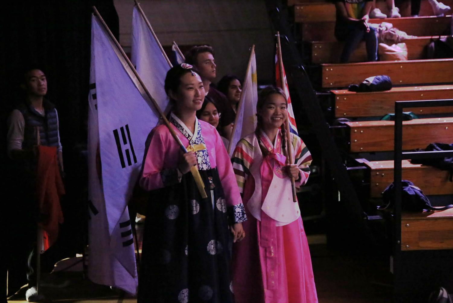 Students+in+traditional+Korean+clothing+carry+the+North+and+South+Korean+flags+in+preparation+to+run+hand+in+hand+in+the+Parade+of+Nations.