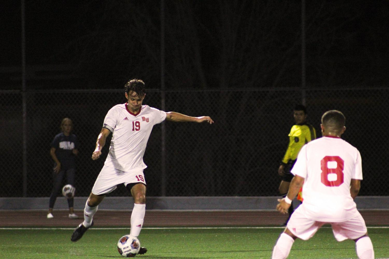Senior defender Jake Munivez kicks the ball to his teammate sophomore midfielder Gio Passarelli.