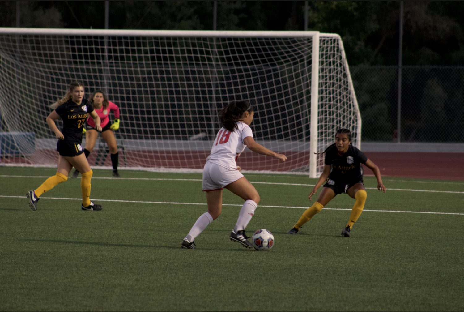 Senior forward Sarah Yang dribbles ball past her opponents.