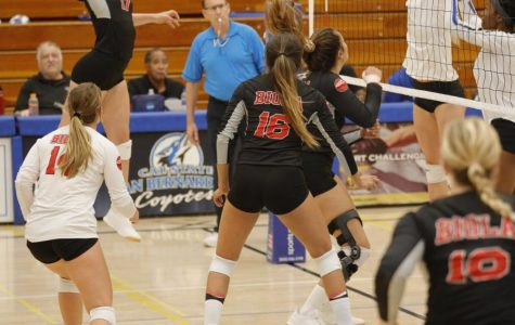 Biola volleyball athlete jumps to spike the ball.