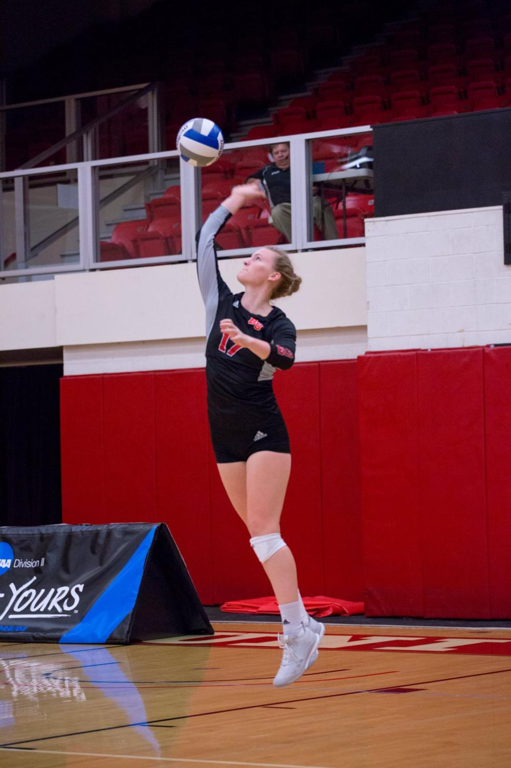 Junior middle blocker, Bekah Roth, serves the ball.
