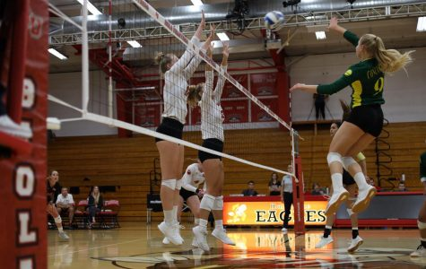 Freshman middle blocker Abigail Copeland and junior middle blocker Bekah Roth jump to block a spike.