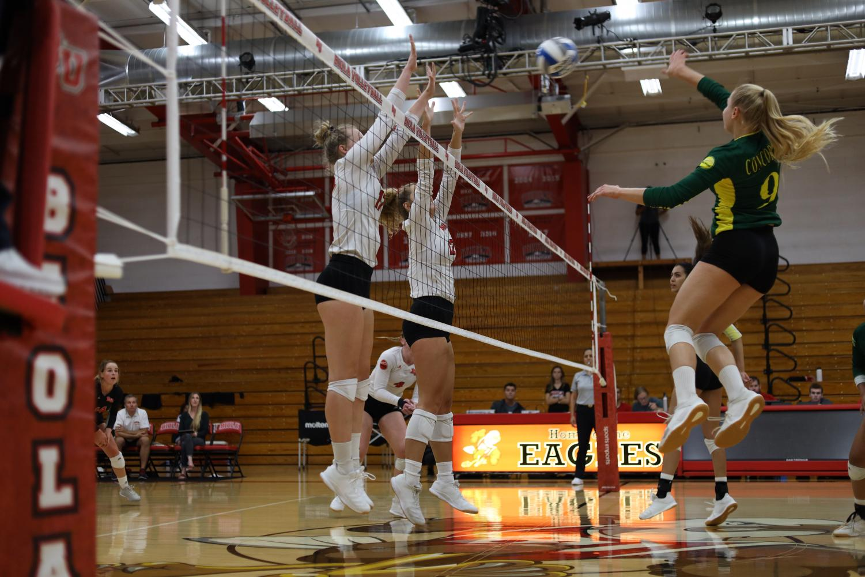 Freshman middle blocker Abigail Copeland and junior middle blocker Bekah Roth jump to block a spike.