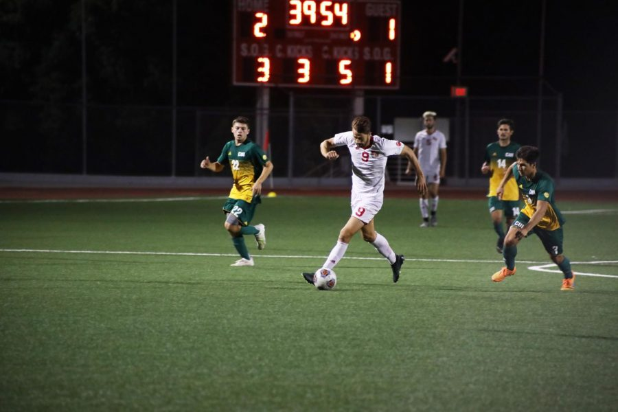 Senior forward Leo Thompson dribbles the ball to the goal.