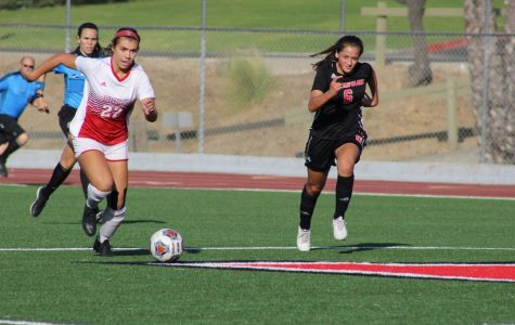 Senior Forward Annmarie Alvarez dribbles the ball down the field.