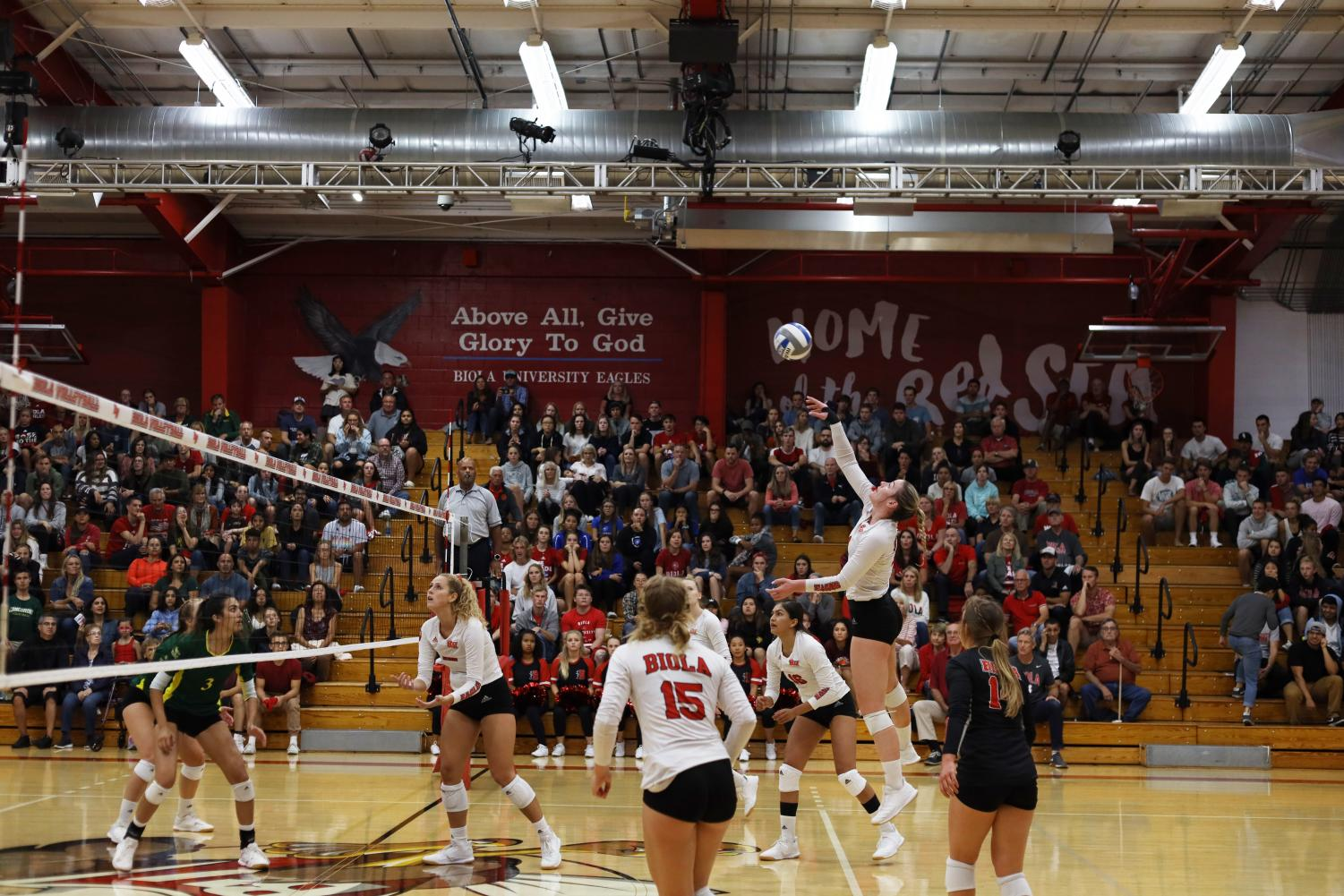A Biola volleyball player jumps for the ball.