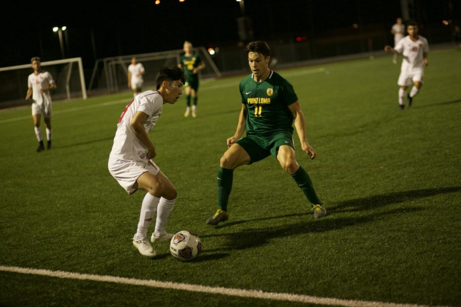 Sophomore forward Hann Kim dribbles the ball around his opponent from Point Loma Nazarene University on November 13th 2019.