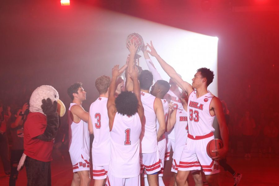 Biola Men's Basketball team holds up their trophy after winning the 3-point contest at Midnight Madness 2019.