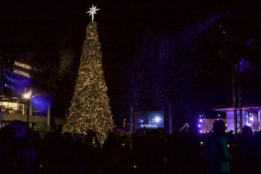 Biola students, faculty, parents, and alumni gather around the lit Christmas tree enjoying the light, fake snow, and fellowship