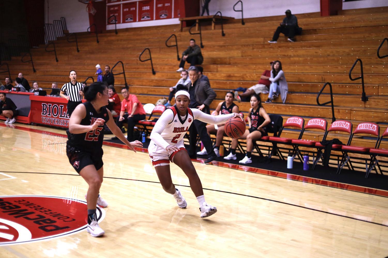 Senior guard Jelissa Puckett dribbles the ball around her opponent.