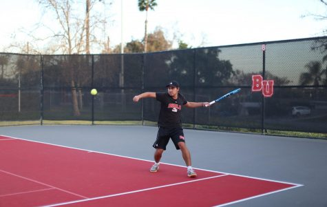 Andres Meneses, a sophomore business major, prepares to swing at the ball.