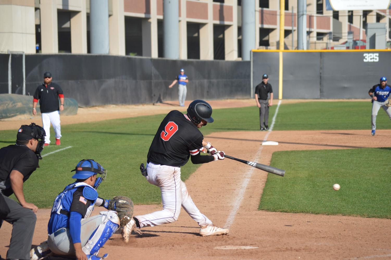 Junior catcher Ben Smith hits the ball.