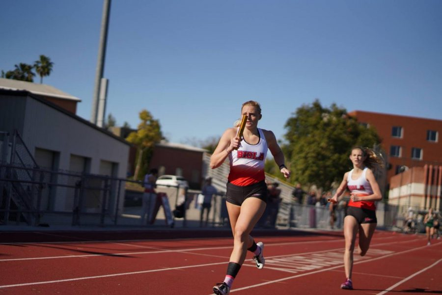 Two members of Biola's track team run the relay.