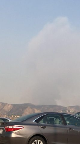 Smoke fills the horizon as evacuees escape raging fires.