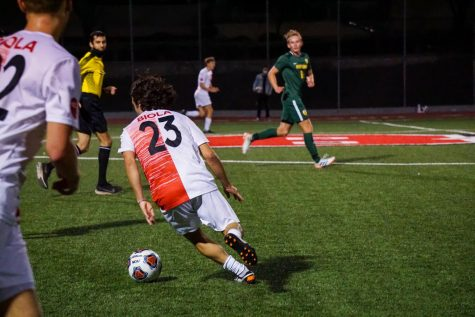 Junior midfielder Aidan Hill in possession of the ball against PLNU.